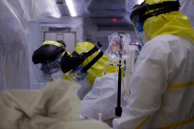 Archivo - Sanitarios del SUMMA protegidos con un traje protector frente al Covid-19 trasladan a un paciente desde la UVI de IFEMA al interior de la unidad móvil para su posterior traslado al Hospital Puerta de Hierro, en Madrid