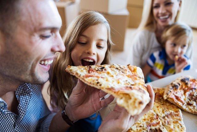 Archivo - Familia feliz comiendo pizza