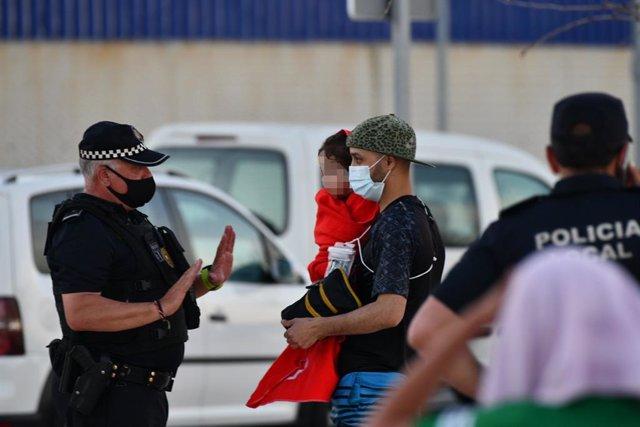 Un policia amb un migrant a la platja del Tarajal, el 17 de maig del 2021, a Ceuta (Espanya).