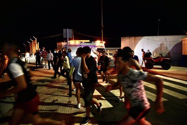 Un grup de migrants arriba a la platja del Tarajal, a Ceuta.