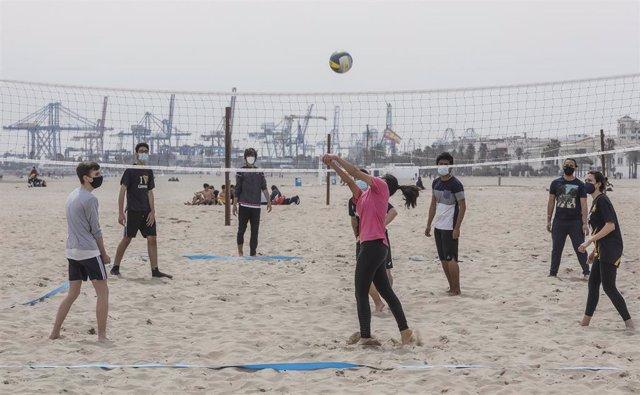 Archivo - Una grupo de varias personas juegan al voleibol con mascarilla en la playa la Malvarrosa en València.