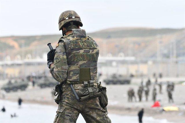 Un militar de l'Exèrcit vigila durant les devolucions en calent a Ceuta.