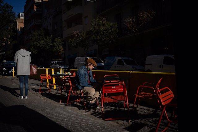 Archivo - Arxiu - Un home assegut en una terrassa a Barcelona.