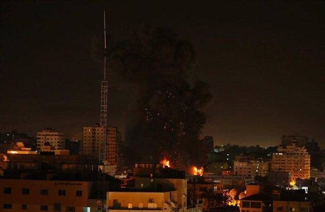El fuego y el humo se elevan por encima de los edificios tras un ataque aéreo israelí, en medio de la escalada de violencia israelí-palestina.