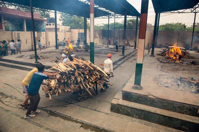 Transporte de madera para la incineración de muertos por coronavirus en un crematorio en India