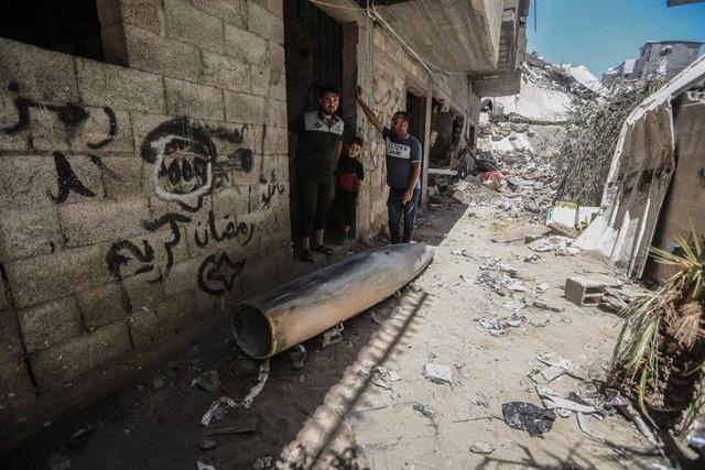 Palestinos junto a una bomba sin estallar lanzada por Israel contra la Franja de Gaza