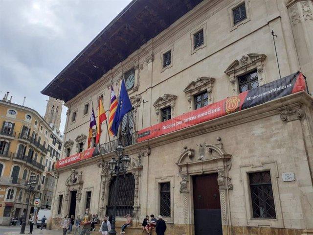 La fachada del Ayuntamiento de Palma luce la bandera de apoyo al Real Club Mallorca.
