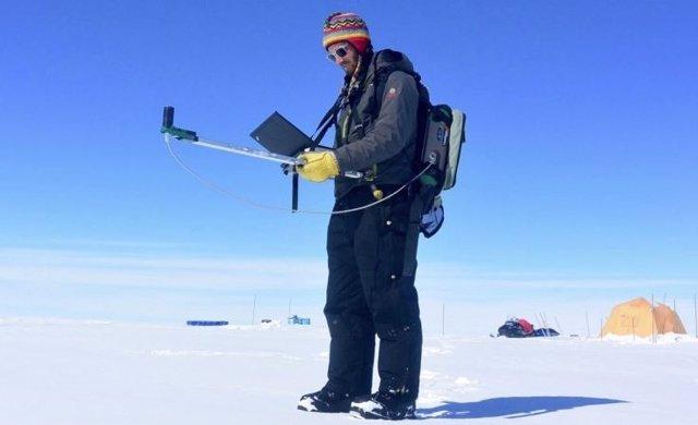 El investigador Gabriel Lewis mide la reflectividad en la capa de hielo de Groenlandia durante una expedición de investigación de 2016.