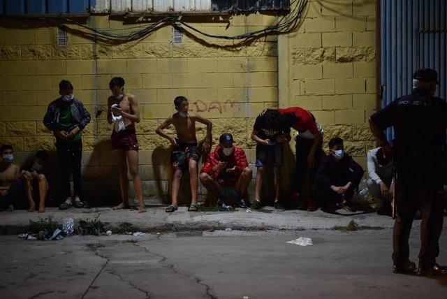 Persones migrants descansen després de la seva arribada a la platja del Tarajal, a Ceuta.