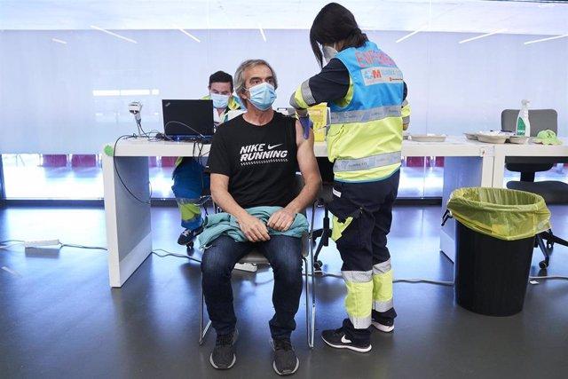 Una sanitario vacuna a un hombre con la dosis de Pfizer en el Wanda Metropolitano, a 19 de mayo de 2021, en Madrid (España). La Comunidad de Madrid comenzó a vacunar el pasado lunes a las personas de entre 50 y 59 años en los hospitales públicos de la reg