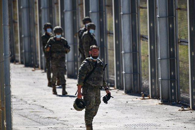 Un grup de militars vigila l'arribada de migrants des de la tanca que separa Ceuta del Marroc, 19 de maig del 2021.