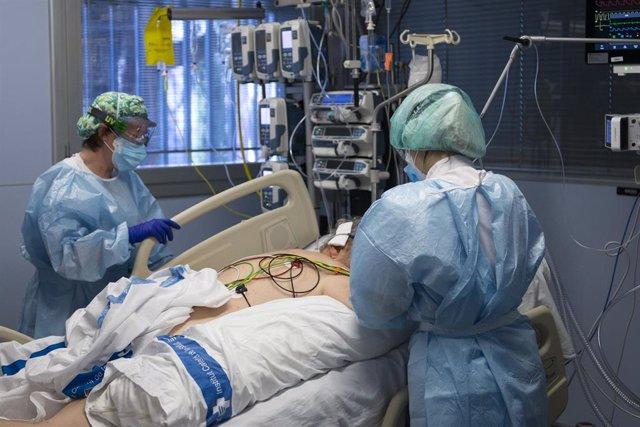 Personal sanitario atendiendo a un paciente ingresado en la Unidad de Cuidados Intensivos (UCI) para enfermos de coronavirus.
