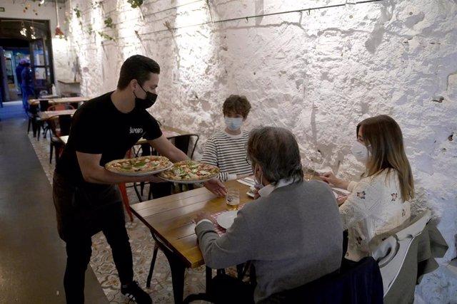 Archivo - Unas personas cenando en el interior de un restaurante