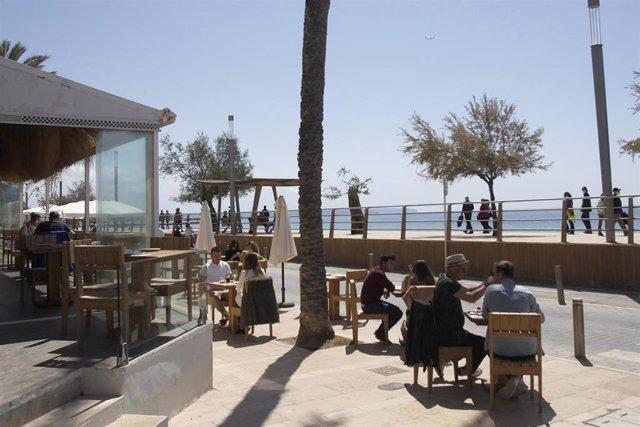 Archivo - Varias personas en la terraza de un bar.