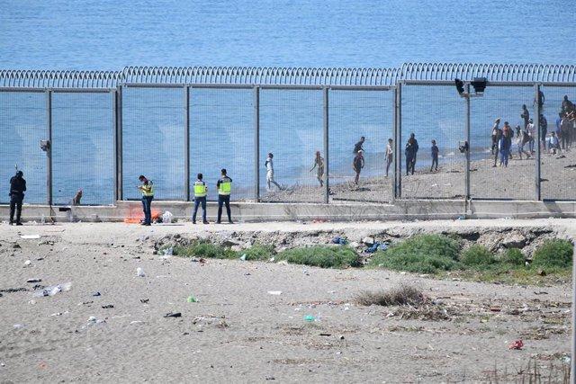 Agentes vigilan desde la valla que separa Ceuta de Marruecos la llegada de migrantes, a 19 de mayo de 2021, en Ceuta, (España). Los intentos de llegar a Ceuta no han cesado desde el lunes y pasadas 72 horas el balance de migrantes que han llegado a territ