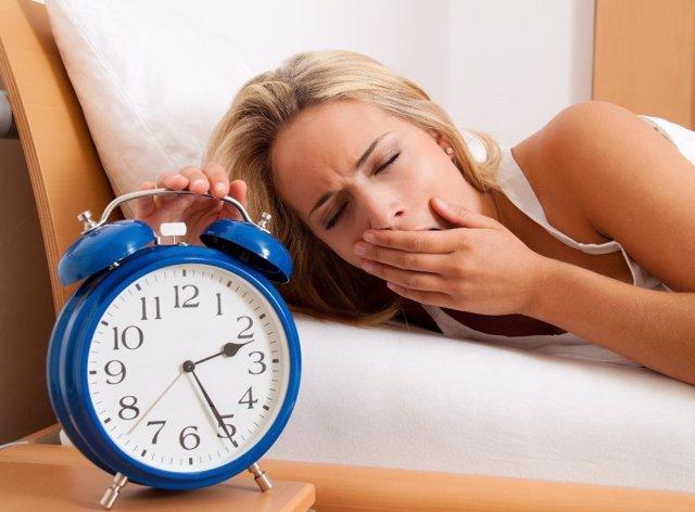 Archivo - Una mujer en la cama apaga el despertador