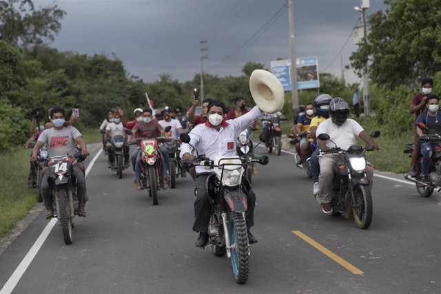 Pedro Castillo a lomos de una motocicleta con un grupo de incondicionales