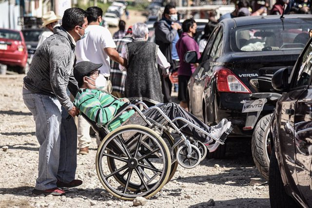 Archivo - 13 March 2021, Mexico, Xalapa: A man pushes an elderly man on a wheelchair as he waits to receive the COVID-19 vaccine at a vaccination clinic. Photo: Hector Adolfo Quintanar Perez/ZUMA Wire/dpa