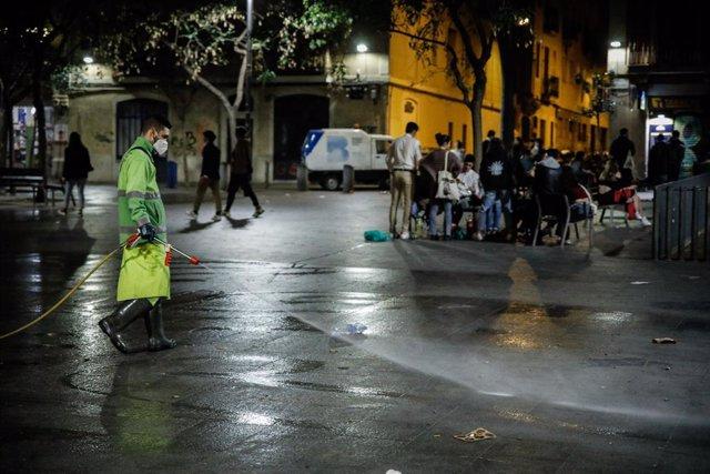 Un home rega un carrer de Barcelona, una setmana després de la fi de l'estat d'alarma, a Barcelona