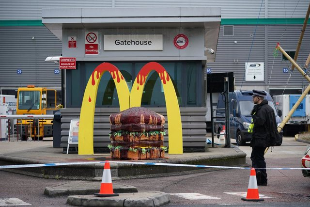 22 May 2021, United Kingdom, Hemel Hempstead: A police officer stands in front of a cordon around Animal Rebellion protesters outside a McDonald's distribution site which is being blockaded to stop lorries from leaving the depot. Photo: Yui Mok/PA Wire/dp