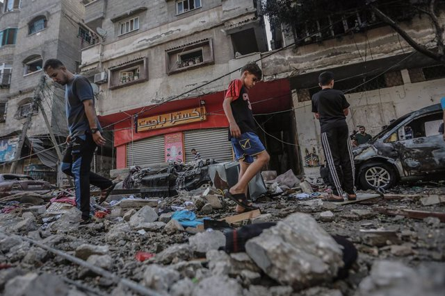 19 May 2021, Palestinian Territories, Gaza City: Palestinians inspect the remains of a destroyed residential building, after it was hit by Israeli airstrikes, amid the escalating flare-up of Israeli-Palestinian violence. According to the Palestinian autho