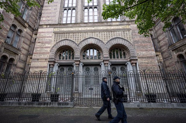 14 May 2021, Berlin: Two policemen walk past the entrance to the New Synagogue Berlin. Photo: Fabian Sommer/dpa