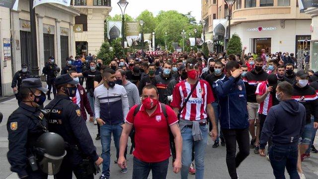 Aficionados del frente Atlético escoltados por agentes de la Policía Nacional a su paso por Valladolid.