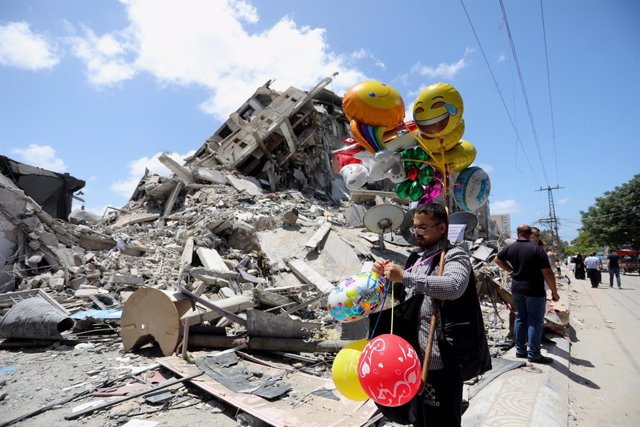 22 May 2021, Palestinian Territories, Gaza: A Palestinian vendor walks past by the ruins of a destroyed building following the Egypt-brokered ceasefire agreement between the Israeli government and the Palestinian Hamas Islamist movement. Photo: Ashraf Amr