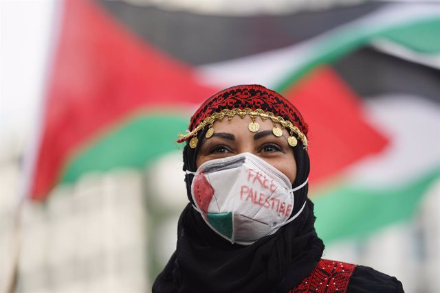 """22 May 2021, Berlin: """"Free Palestine"""" is seen written on a woman's face mask as she takes part in a rally of Palestinian supporters at Potsdamer Platz. The demonstration was held under the slogan """"Protest rally against Israeli aggression in Palestine"""". Ph"""