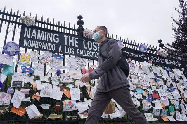 Archivo - Un hombre con mascarilla junto a un memorial en recuerdo a los fallecidos por coronavirus en EEUU