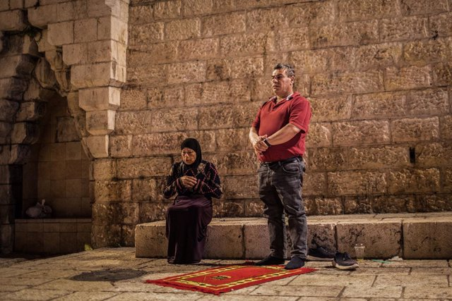 07 May 2021, Israel, Jerusalem: Muslims perform the 'Tarawih' evening prayers of the holy fasting month of Ramadan near the Al-Aqsa Mosque compound. Photo: Ilia Yefimovich/dpa