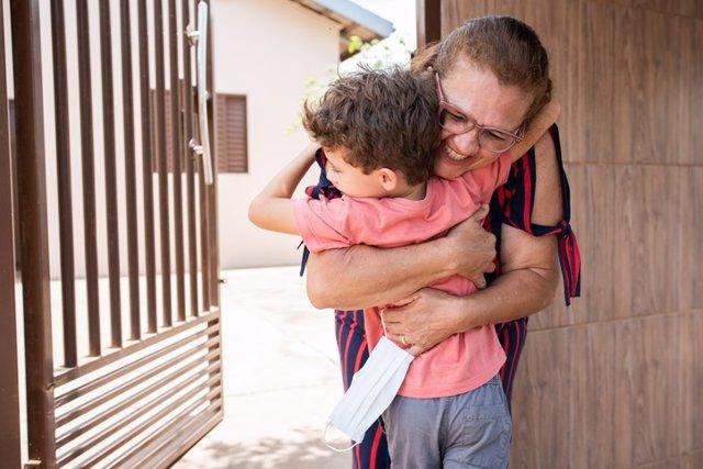 Archivo - Abuela abrazando a su nieto con la mascarilla en la mano.