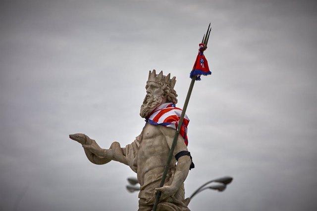 La estatua de la fuente de Neptuno, con una bufanda del Atlético de Madrid, a 23 de mayo de 2021, en Madrid (España). Esta bufanda en la estatua de Neptuno es resultado de las celebraciones, durante la noche de este sábado, por la victoria del club rojibl