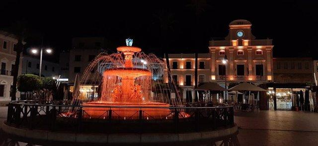 Fachada del Ayuntamiento de Mérida y fuente iluminada de naranja por el Día Nacional de la Epilepsia