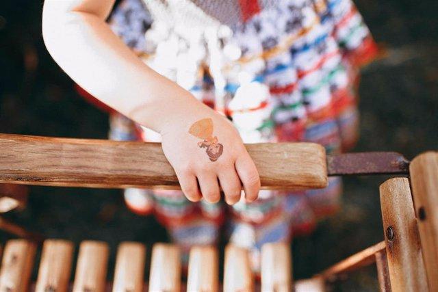 Imagen de recurso de una niña con una calcomanía en la mano