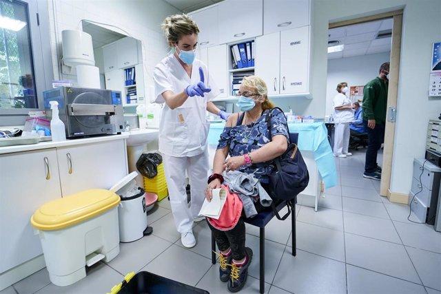 Una sanitaria vacuna a una mujer sin hogar en el Centro de Acogida Municipal Para Personas Sin Hogar San Isidro, a 20 de mayo de 2021, en Madrid (España). La visita coincide con el inicio de la vacunación para personas sin hogar en los centros municipales