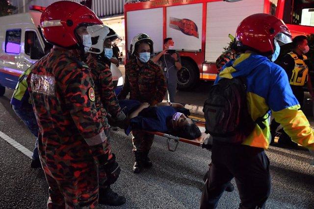 24 May 2021, Malaysia, Kuala Lumpur: Emergency workers carry an injured passenger after two Light Rail Transit (LRT) trains collided near the Kampung Baru station. Photo: Hazim Mohammad/BERNAMA/dpa