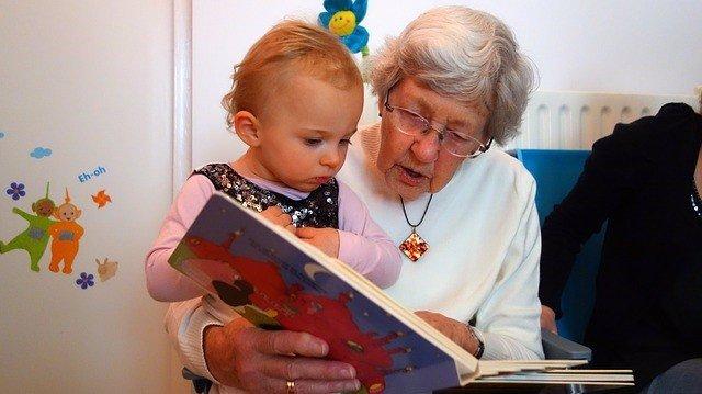 Archivo - Una mujer mayor cuenta un cuento a una niña.
