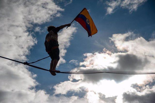 Un manifestante camina sobre la cuerda floja mientras agita la bandera colombiana en el estadio de fútbol El Campín durante una manifestación contra el Gobierno del presidente Iván Duque.