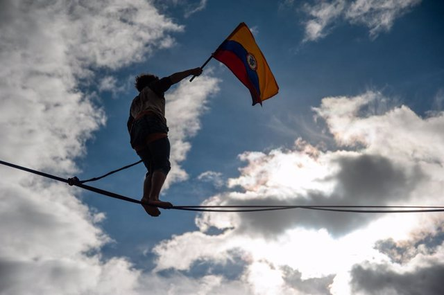 19 May 2021, Colombia, Bogota: A protester walks on a tightrope while waving the Colombian flag at El Campin Football Stadium during a demonstration against the government of President Ivan Duque Marquez. Photo: Chepa Beltran/LongVisual via ZUMA Wire/dpa