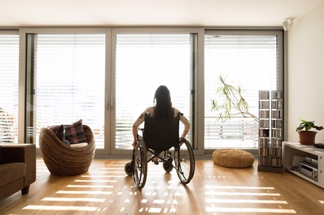 Archivo - Young disabled woman in wheelchair at home, rear view.