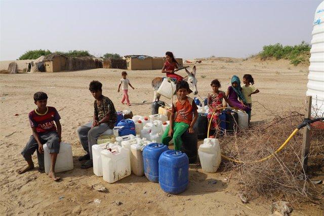 Archivo - Niños esperan para llenar bidones de agua en Yemen
