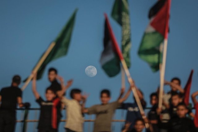 24 May 2021, Palestinian Territories, Gaza City: Supporters of the Palestinian Hamas Islamist movement hold flags during a rally by Hamas military wing 'Izz ad-Din al-Qassam Brigades' to commemorate the martyrs of the last battle between Hamas and Israel.