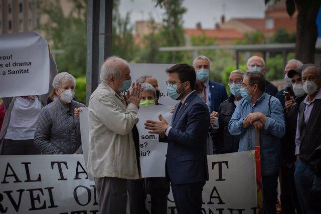 """El president de la Generalitat Pere Aragonès (d) parla amb un veí durant una concentració per la sanitat """"100% pública"""" abans de la seva visita a l'Hospital Parc Taulí l'endemà de prendre possessió del càrrec."""