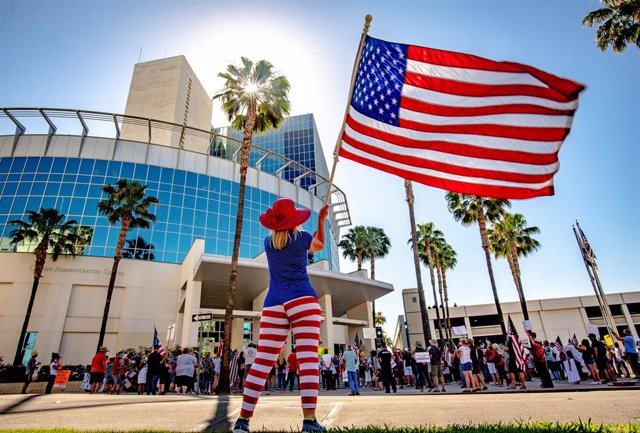 Archivo - 05 May 2020, US, Riverside: Awoman waves the US national flag in front of the Riverside County Administration building during a demonstration against the Coronavirus exit restrictions. Photo: Watchara Phomicinda/Orange County Register via ZUMA/