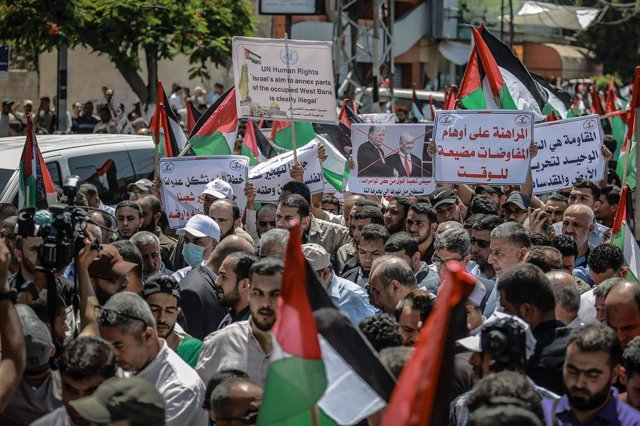 """Archivo - 01 July 2020, Palestinian Territories, Gaza City: Palestinians wave national flags and hold placards as they take part in the """"Day of Rage"""" demonstration to protest against the Israeli annexation plan that will occupy about 30 percent of the Wes"""