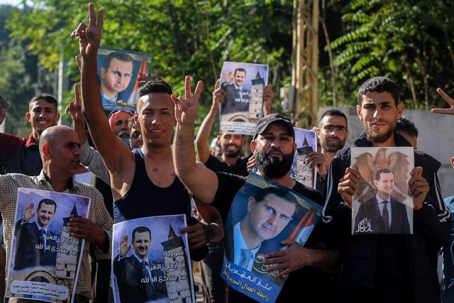 20 May 2021, Lebanon, Baabda: Syrians carry pictures of Syrian President Bashar al-Assad while heading to cast their votes during the first stage of the Syrian Presidential election at the Syrian Embassy. Photo: Marwan Naamani/dpa