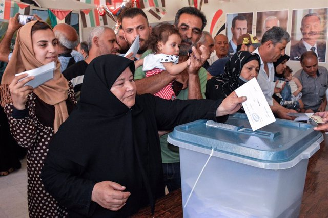 HANDOUT - 26 May 2021, Syria, Homs·: A picture provided by the Syrian Arab News Agency (SANA) shows a woman casting her ballot at a polling station during the Syrian presidential election. Photo: -/SANA/dpa - ATTENTION: editorial use only and only if the