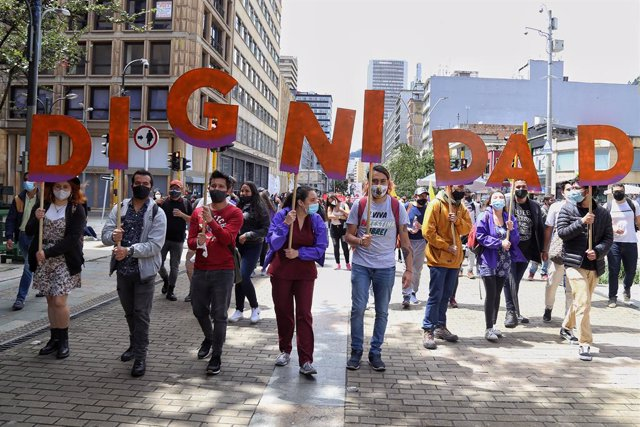 """26 May 2021, Colombia, Bogota: Young protesters carry letters forming the word """"dignity"""" during a demonstration against the government of President Ivan Duque Marquez. Photo: Camila Díaz/colprensa/dpa"""