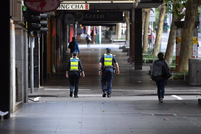 """Archivo - Police officers walk up Swanston Street in Melbourne, Saturday, February 13, 2021. Victoria has entered a """"short, sharp circuit-breaker"""" lockdown for five days amid fears the highly infectious UK strain of coronavirus has spread in the community"""